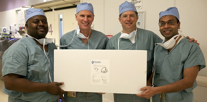 From left: Eugene Thomas, James Geiger, Greg Bowles and Shorya Awtar hold an unopened package with a FlexDex instrument inside as they stand outside of a University of Michigan Hospital surgery room where the instrument will be used for the first time in surgery.